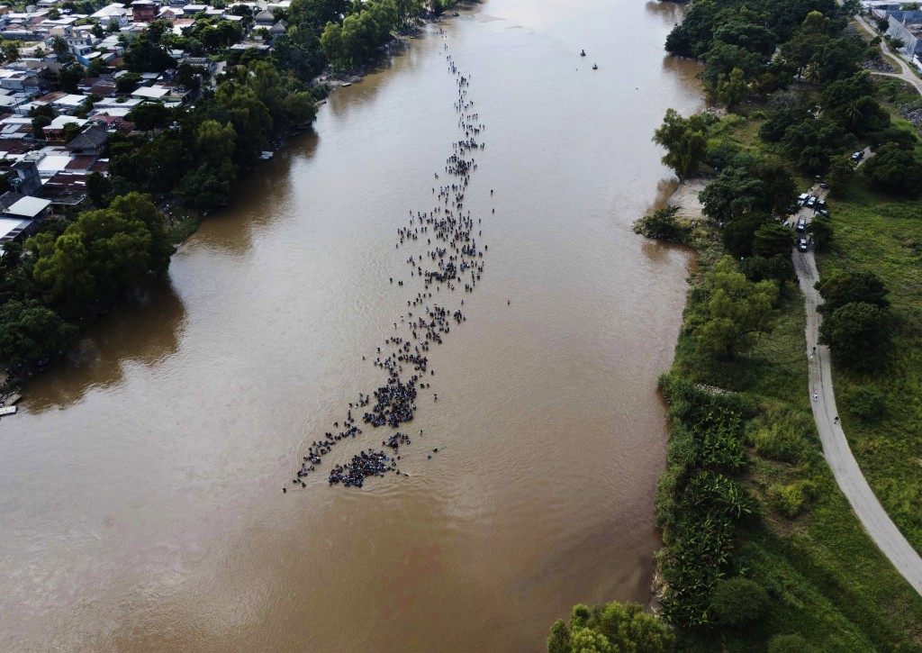 A group of Central American migrants bound for the U.S. border wade together across the Suchiate River, which connects Guatemala and Mexico, in Tecun