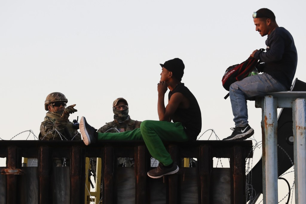 U.S. Border Patrol agents, left, speak with two Central American migrants as they sit atop the border structure separating Mexico and the United State...