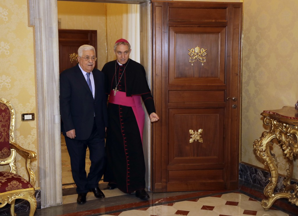 Palestinian President Mahmoud Abbas, left, is flanked by Vatican Prefect of the Pontifical Household, Archbishop Georg Ganswein, as he arrives for a p