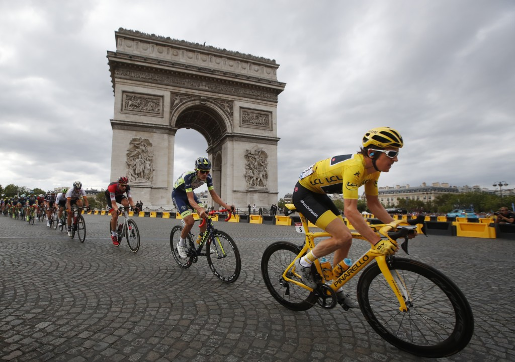Tour de France winner Geraint Thomas, of Britain, wearing the overall leader's yellow jersey, passes the Arc de Triomphe on July 29, 2018, during the ...
