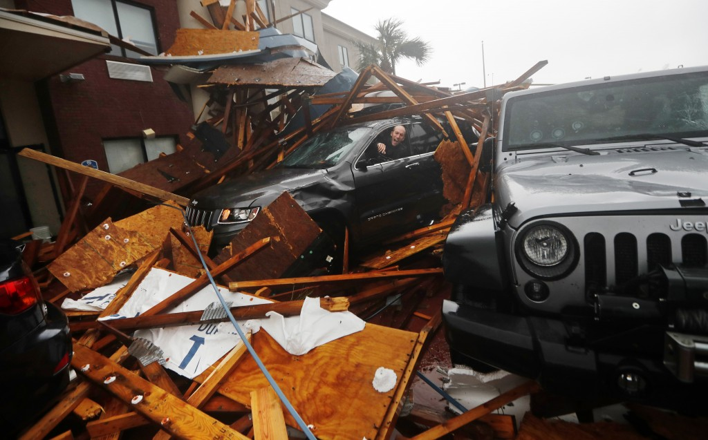 A storm chaser climbs into his vehicle to retrieve equipment after a hotel canopy collapsed, as the eye of Hurricane Michael passes over Panama City B