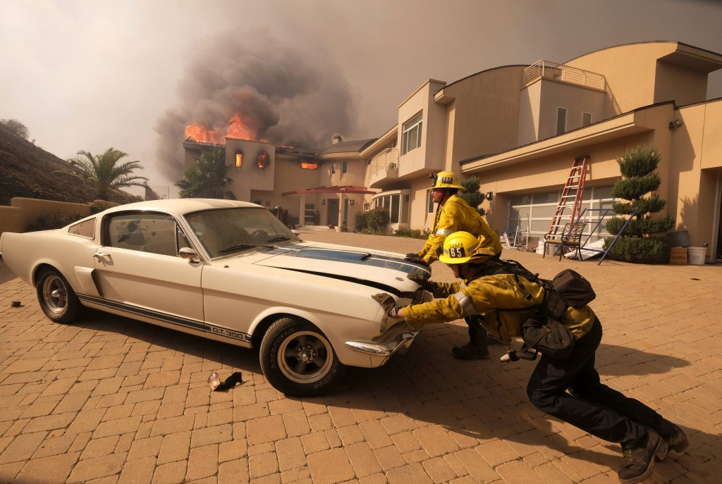 Firefighters push a car from a garage as a wildfire fire burns a home in Malibu, Calif., on Nov. 9, 2018. (AP Photo/Ringo H.W. Chiu)