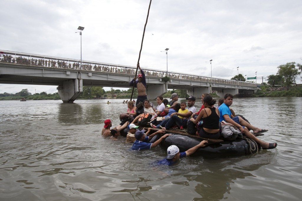 A group of Central American migrants cross the Suchiate River aboard a raft made out of tractor inner tubes and wooden planks, on the the border betwe...