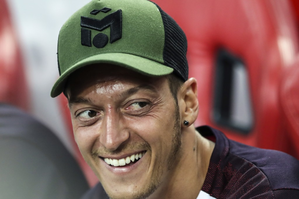 FILE - In this Thursday, July 26, 2018 file photo, Arsenal's Mesut Ozil smiles on the bench during the International Champions Cup match between Arsen...