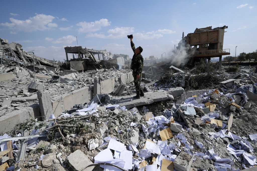 A Syrian soldier films the wreckage of the Syrian Scientific Research Center, which was attacked by U.S., British and French military strikes to punis