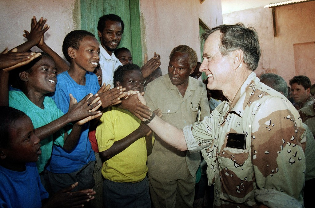 FILE - In this Jan. 1, 1993, file photo, U.S. President George H.W. Bush greets Somali children applauding him during a visit to an orphanage in famin