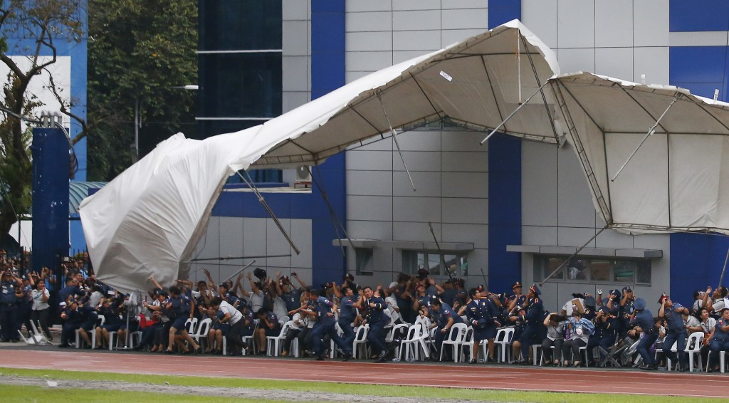 Philippine National Police officers and employees react as their tent is toppled by the downwash of a hovering police helicopter performing a salute d