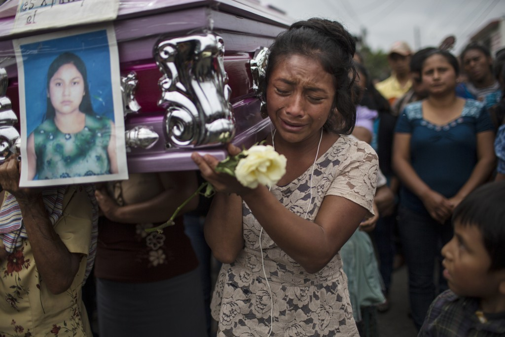 """Yoselin Rancho cries while carrying the remains of her best friend, Etelvina Charal, who died in the eruption of the Volcan de Fuego, or """"Volcano of F"""