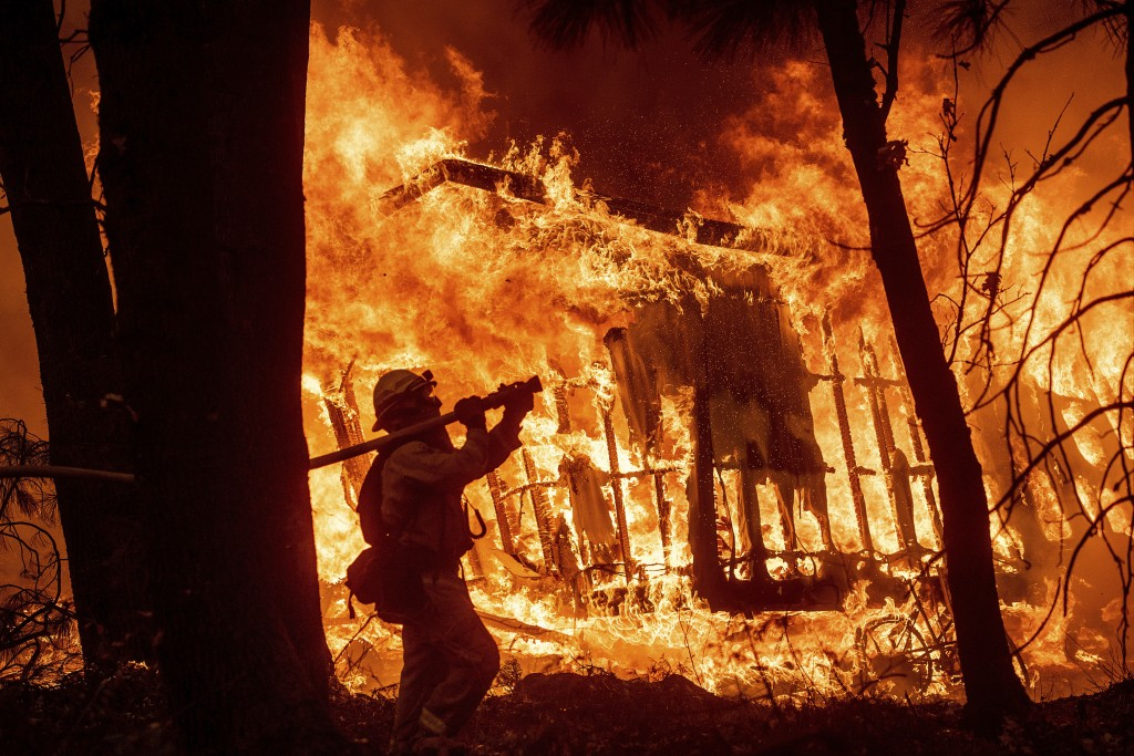 Firefighter Jose Corona sprays water as flames from the Camp Fire consume a home in Magalia, Calif., on Nov. 9, 2018. (AP Photo/Noah Berger)