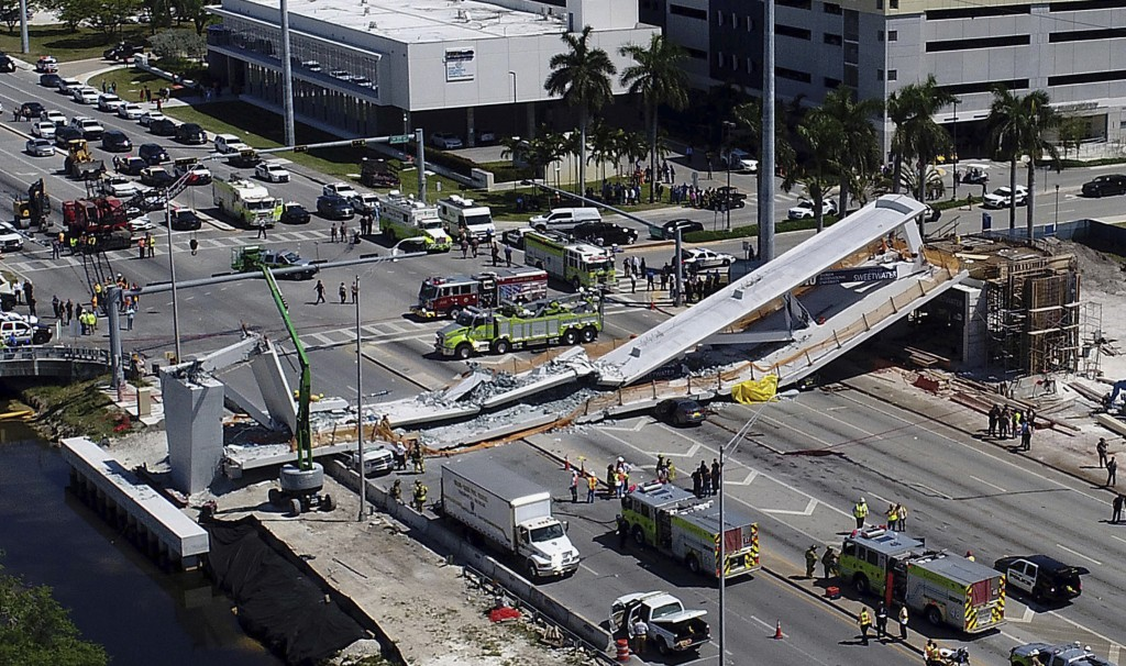 Emergency personnel respond after a brand-new pedestrian bridge collapsed onto a highway at Florida International University in Miami, crushing cars a...