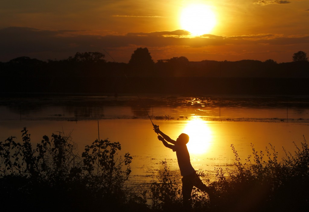 In this Monday, Dec, 3, 2018, file photo, a fisherman casts his line out on a lake during sunset in Naypyitaw, Myanmar, Monday, Dec, 3, 2018. (AP Phot