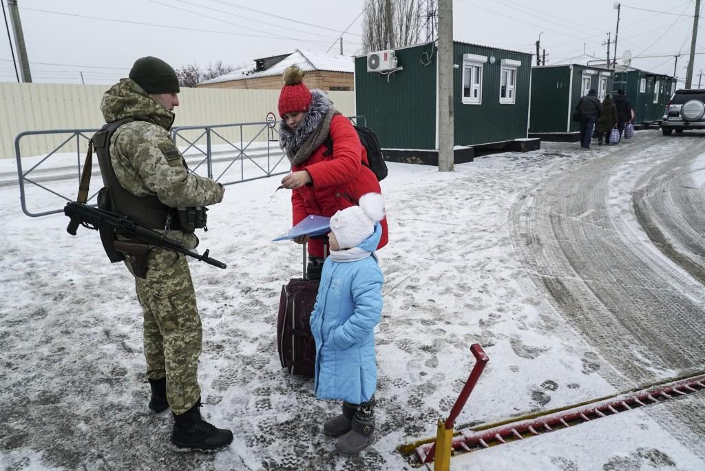 A Ukrainian border guard checks documents of a woman crossing the border the Ukraine - Russia border in Milove town, eastern Ukraine, Sunday, Dec. 2, ...