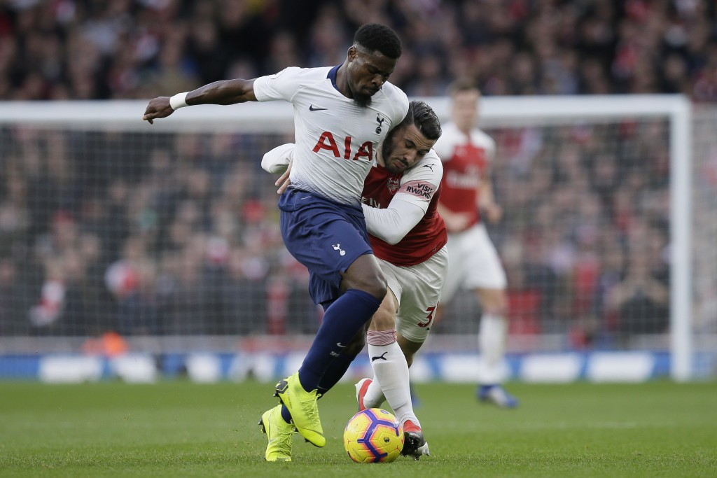 Tottenham's Serge Aurier, left, fights for the ball with Arsenal's Sead Kolasinac during the English Premier League soccer match between Arsenal and T