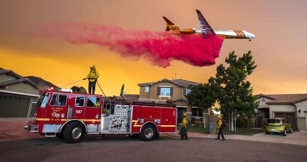 A plane drops fire retardant behind homes along McVicker Canyon Park Road in Lake Elsinore, Calif., as the Holy Fire burned near homes on Aug. 8, 2018...