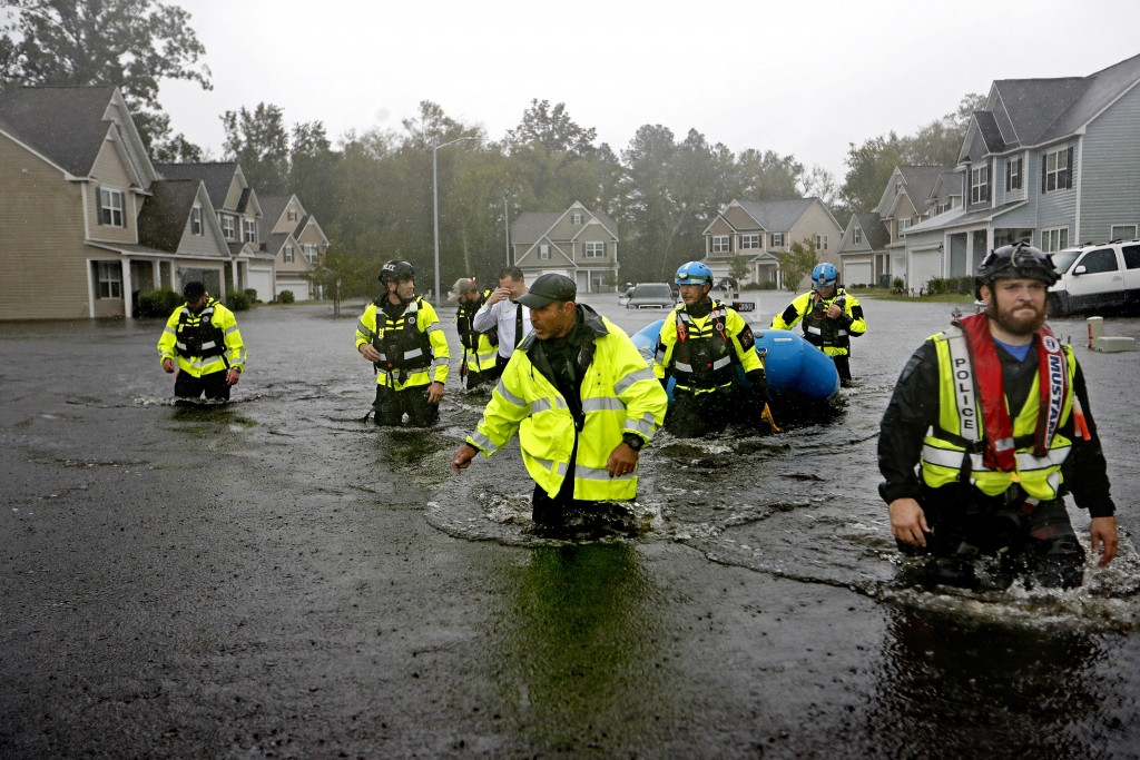 Members of the North Carolina Task Force urban search and rescue team wade through a flooded neighborhood looking for residents who stayed behind as F...