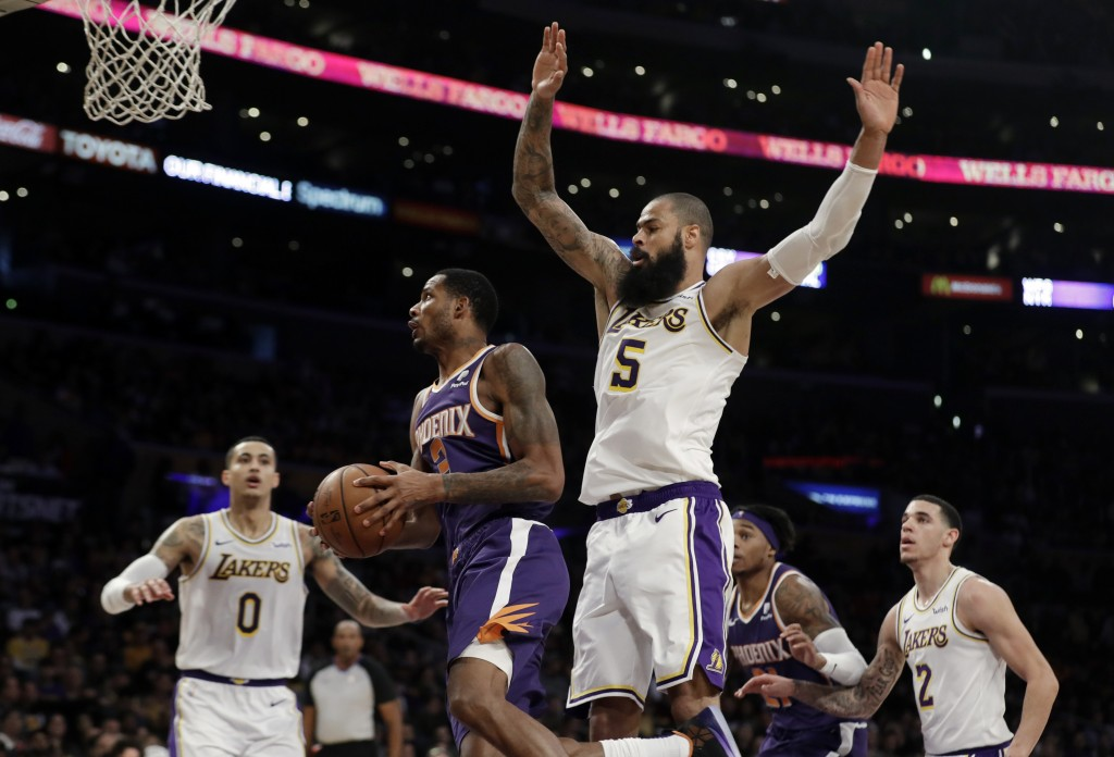 Phoenix Suns' Trevor Ariza, second from left, drives past Los Angeles Lakers' Tyson Chandler (5) during the first half of an NBA basketball game Sunda