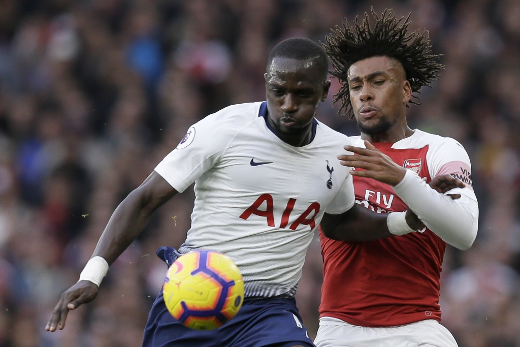 Tottenham's Moussa Sissoko, left, and Arsenal's Alex Iwobi fight for the ball during the English Premier League soccer match between Arsenal and Totte