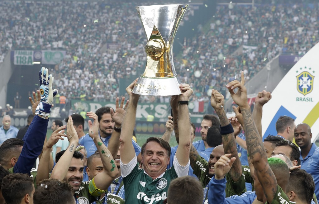 Brazil's President-elect Jair Bolsonaro holds up the Brazilian soccer championship trophy, as he celebrates with Palmeiras soccer club who won the tit...
