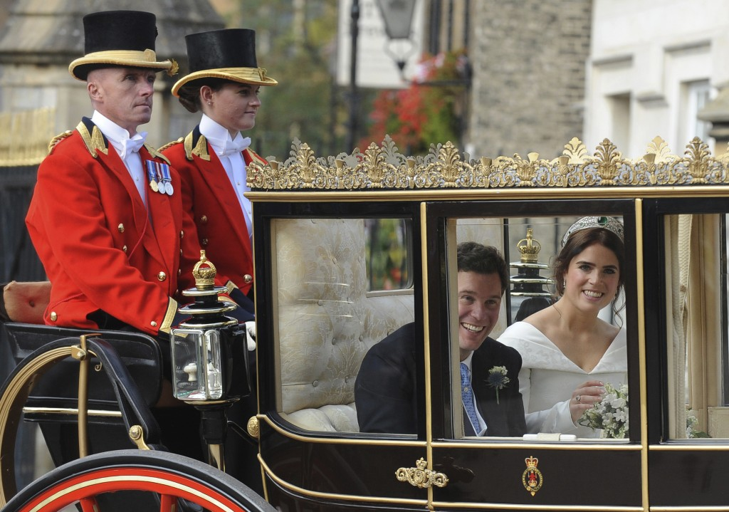 Princess Eugenie of York, right, and Jack Brooksbank look out from their carriage as they travel from St. George's Chapel to Windsor Castle after thei...