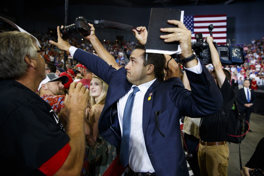 A volunteer member of the advance team for President Donald Trump blocks a camera as a photojournalist attempts to take a photo of a protester during