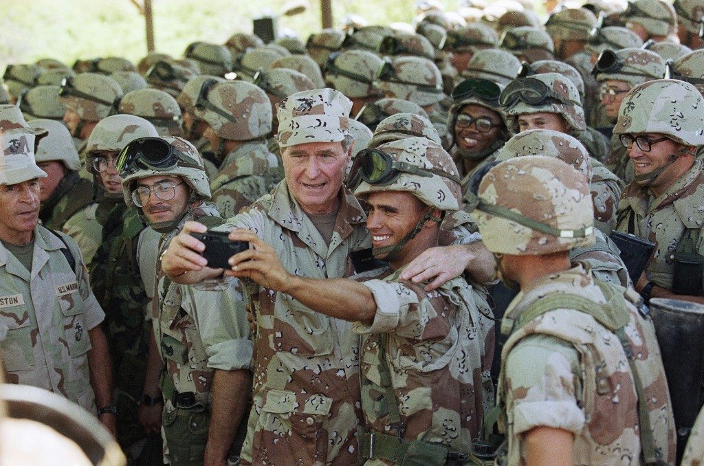 FILE - In this Jan. 1, 1993, file photo, U.S. President George H.W. Bush holds a camera at arm's length for a selfie with Marines at Baidoa's airport