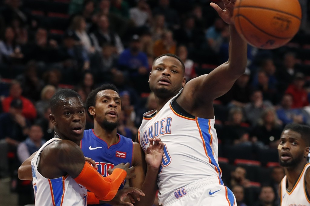 Detroit Pistons guard Ish Smith, center, passes the ball while defended by Oklahoma City Thunder guard Dennis Schroder, left, and guard Deonte Burton,
