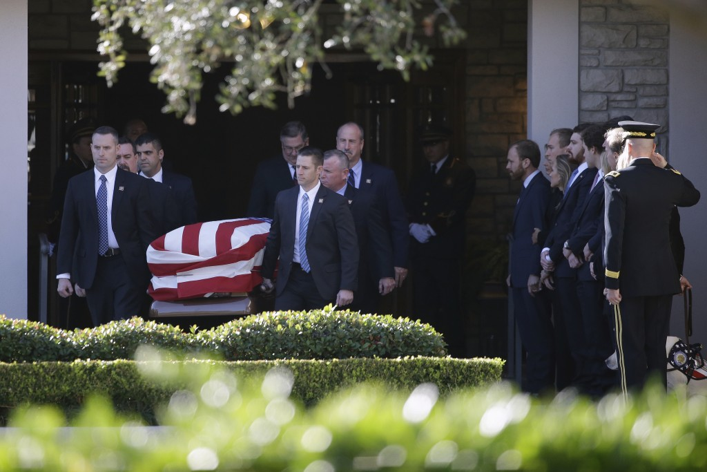 Members of the U.S. Secret Service carry the casket with former President George H. W. Bush to a hearse at George H. Lewis Funeral Home after a family