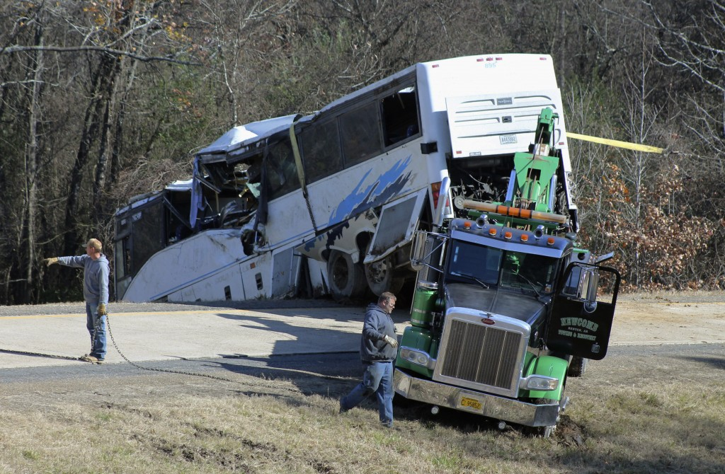 Employees from a wrecker service work to remove a charter bus from a roadside ditch Monday, Dec. 3, 2018, after it crashed alongside Interstate 30 nea