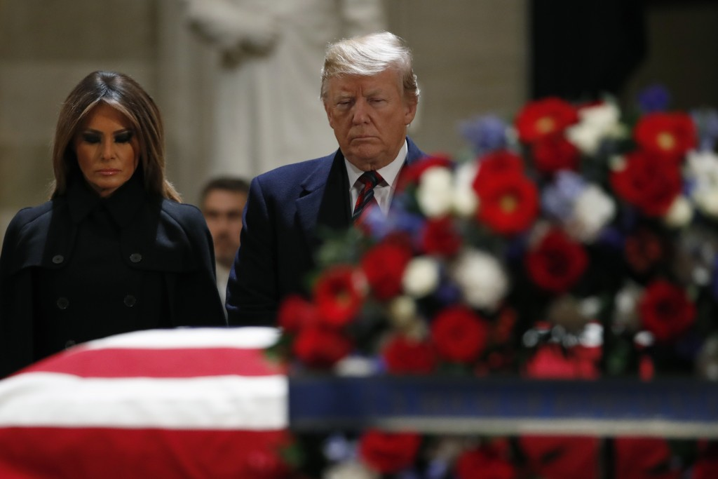President Donald Trump and first lady Melania Trump pay their respects to former President George H. W. Bush, as he lies in state in the Rotunda of th