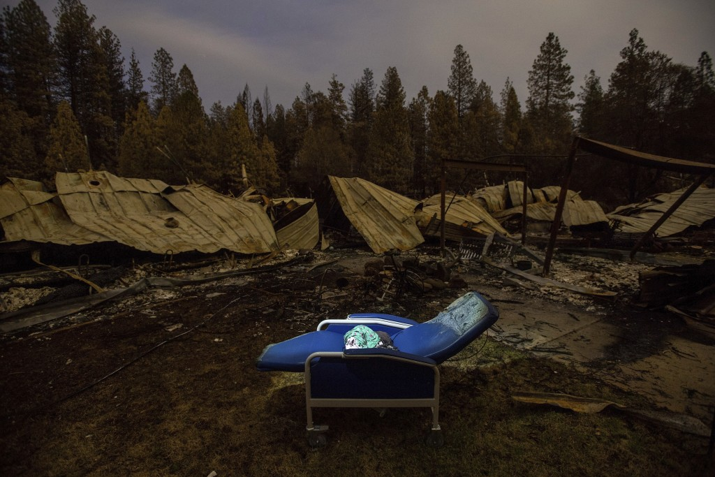 A chair rests outside Cypress Meadows Post-Acute, a nursing home leveled by the Camp Fire, on Tuesday, Dec. 4, 2018, in Paradise, Calif. (AP Photo/Noa