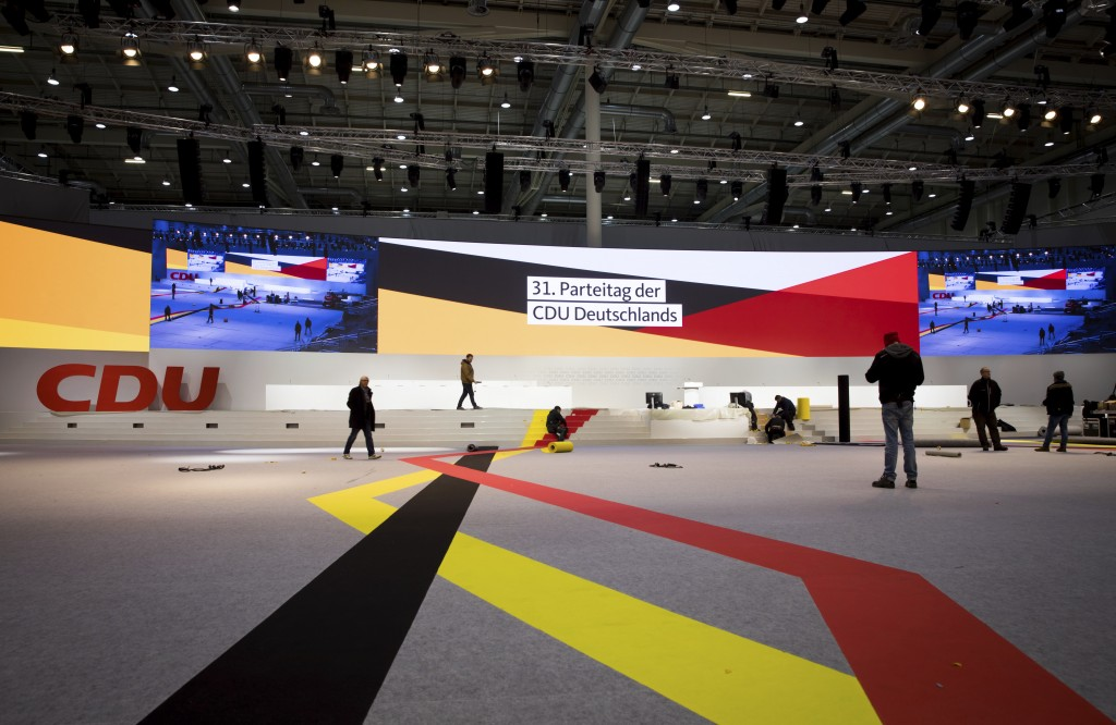 Workers walk through the convention venue during preparations for the 31th party convention of German Christian Democrats (CDU) in Hamburg, Germany, W