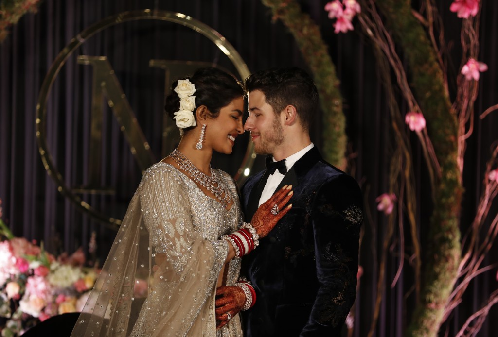 In this Tuesday, Dec. 4, 2018, file photo, Bollywood actress Priyanka Chopra and musician Nick Jonas stand for photographs at their wedding reception