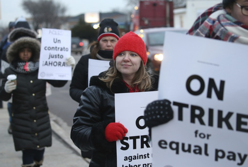 Charter school teachers including Vanessa Cerf-Nikolakakis, center, of Torres Elementary School, and other supporters walk the picket line outside the