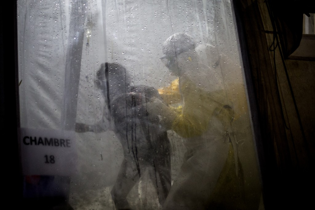 In this photo taken Saturday, Nov. 3, 2018 and made available Tuesday, Dec. 4, 2018, health workers are seen helping an unconfirmed Ebola patient into