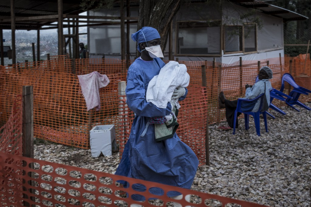 In this photo taken Sunday, Nov. 4, 2018 and made available Tuesday, Dec. 4, 2018, a caretaker already cured of Ebola is seen carrying a four day old
