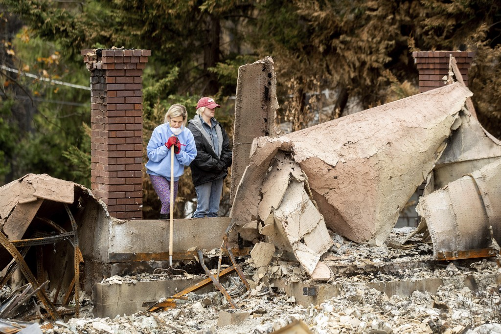 Jean Uno searches for heirlooms at her parent's Magalia, Calif., home, destroyed by the Camp Fire, on Tuesday, Dec. 4, 2018. Uno also lost her home in