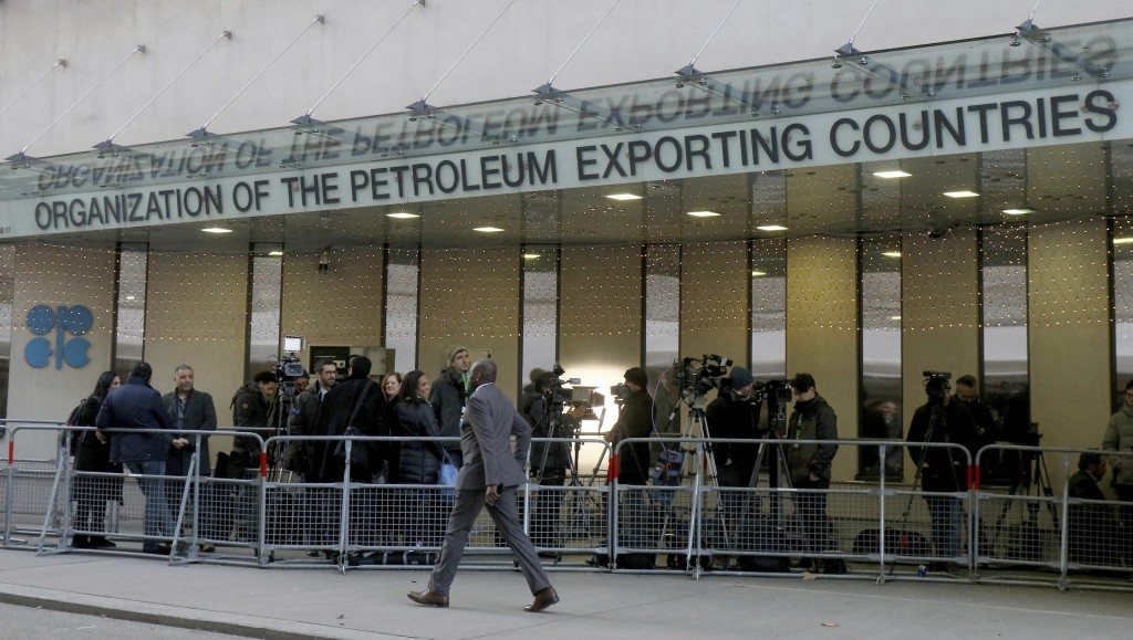 People stand in front of the headquarters of the Organization of the Petroleum Exporting Countries, OPEC, in Vienna, Austria, Wednesday, Dec. 5, 2018.