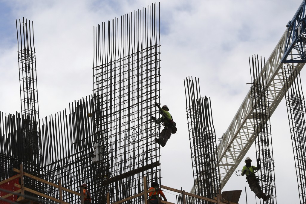 FILE- In this Sept. 24, 2018, photo metal workers are silhouetted on the top of The Rise, a luxury apartment building under construction in Flagler Vi