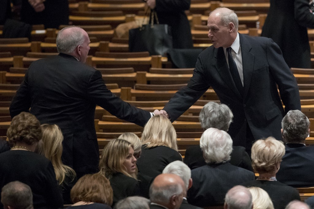 Former CIA Director John Brennan, left, shakes hands with President Donald Trump's Chief of Staff John Kelly, right, before a State Funeral for former