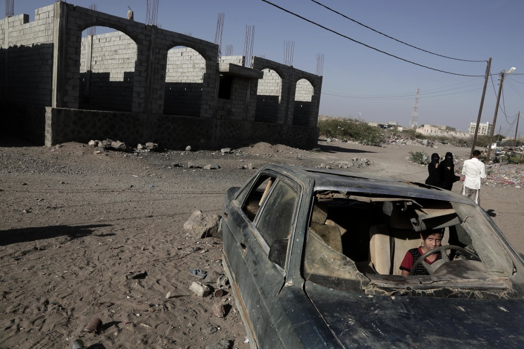FILE - In this Feb. 10, 2018 file photo, a boy sits in a damaged car in Mocha, Yemen. Envoys from Yemen's warring parties are headed to Sweden for ano