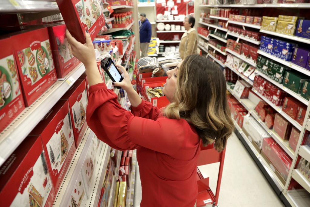 FILE- In this Nov. 16, 2018, file photo Target employee Lindsay Walker scans an item as she collects merchandise from shelves to prep them for an onli
