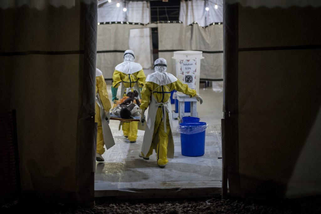 In this photo taken Saturday, Nov. 3, 2018 and made available Tuesday, Dec. 4, 2018, health workers move an Ebola patient inside of a Medecins Sans Fr