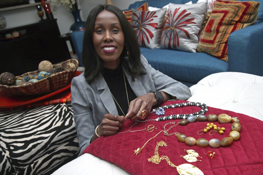 In this Monday, Dec. 3, 2018, photo, Shamila Nduriri, who owns Dalasini, an upscale jewelry company, poses in her Minneapolis apartment with some of h