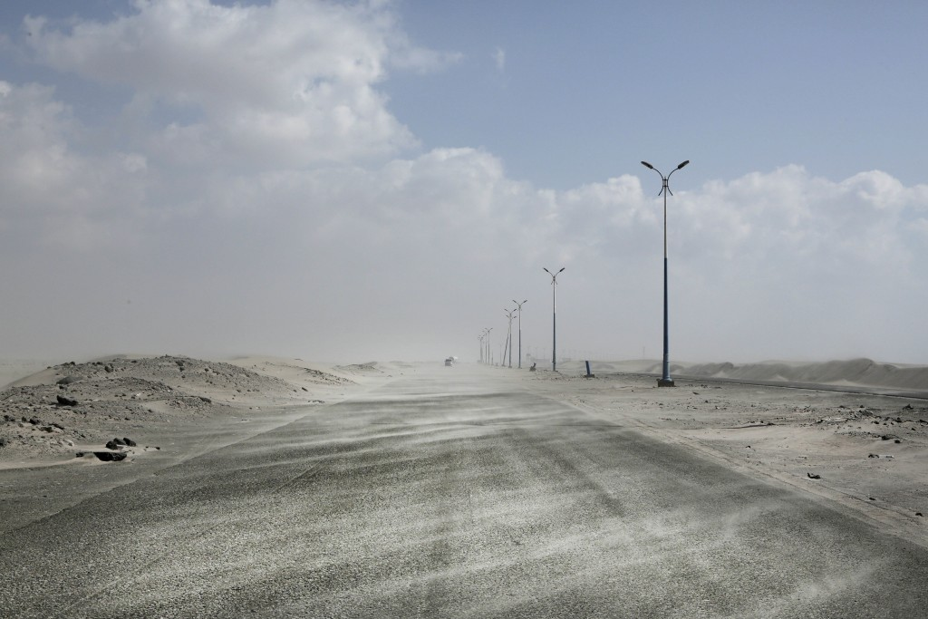 FILE - This Feb. 15, 2018, file, photo shows sand drifting over an empty highway from Abyan to Aden in Yemen. Envoys from Yemen's warring parties are