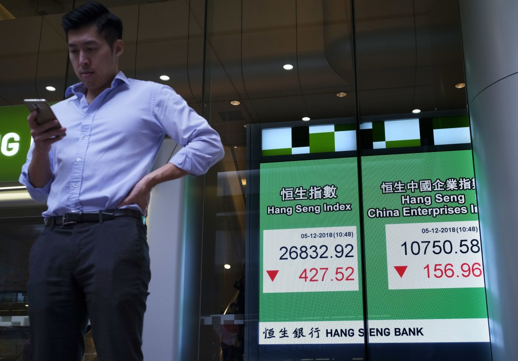 A man stands next an electronic board showing Hong Kong share index outside a local bank in Hong Kong, Wednesday, Dec. 5, 2018. Shares were moderately