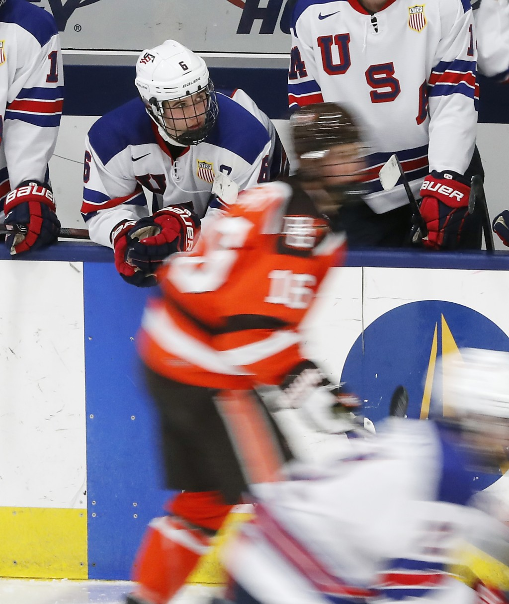 In this Wednesday, Nov. 21, 2018, photo, Jack Hughes, expected to be a top pick in the next NHL hockey draft, watches from the bench during a game aga