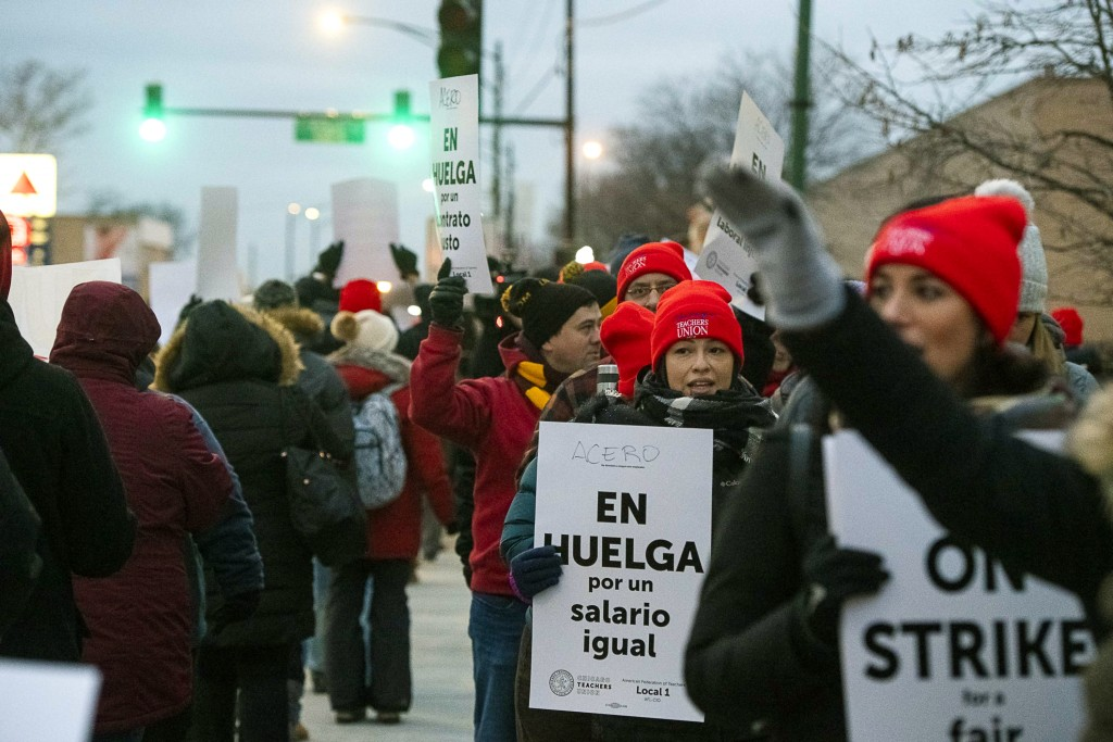 Educators with Acero charter schools strike outside Veterans Memorial Charter School Campus, Tuesday, Dec. 4, 2018, in Chicago. Hundreds of teachers h