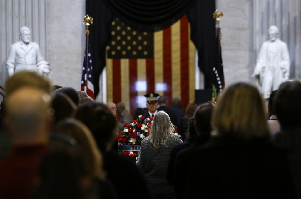 Visitors file into the Capitol Rotunda to view the flag-draped casket of former President George H.W. Bush as he lies in state in Washington, Tuesday,
