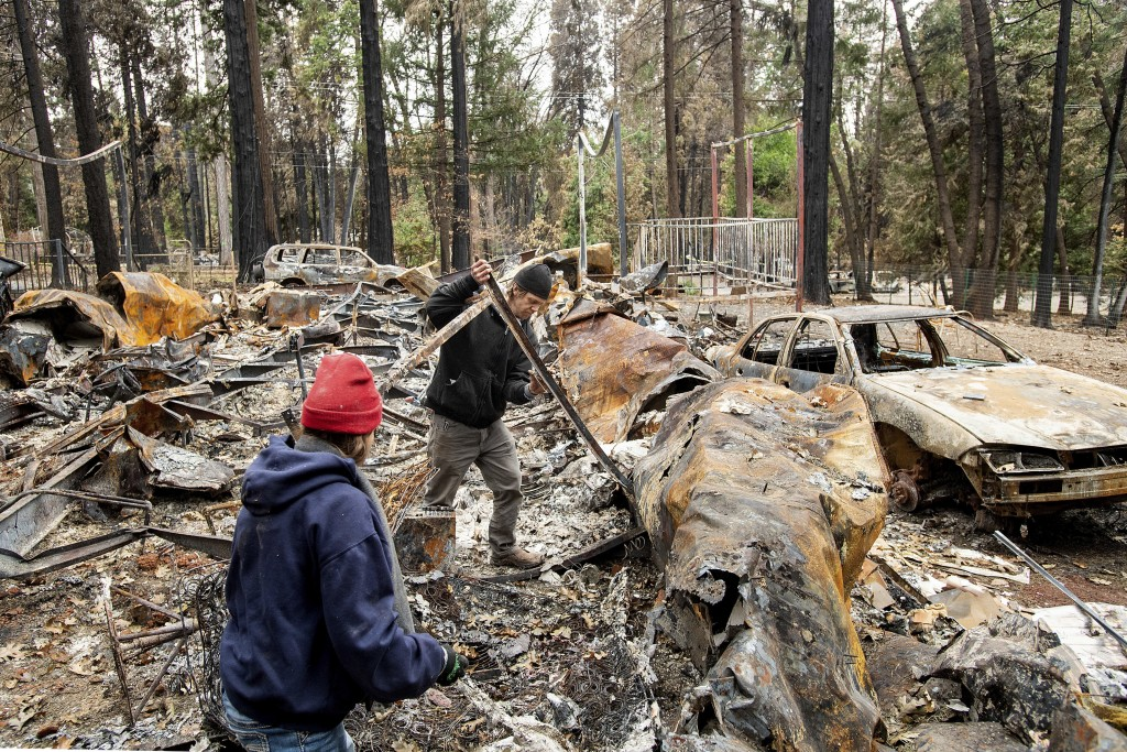 Following the Camp Fire, Jedediah Welch helps his friend Sara Sullivan, left, search for belongings at her Magalia, Calif., home on Tuesday, Dec. 4, 2