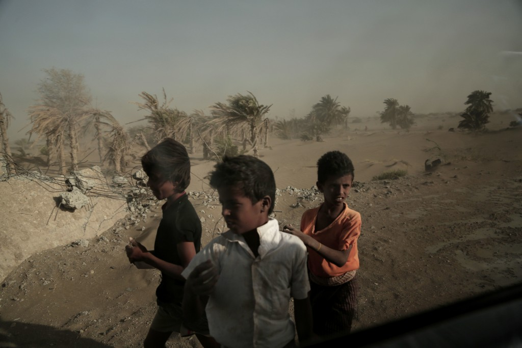 FILE - In this Feb. 12, 2018, file, photo, homeless children stand on the road from Khoukha to Taiz in Yemen. Envoys from Yemen's warring parties are
